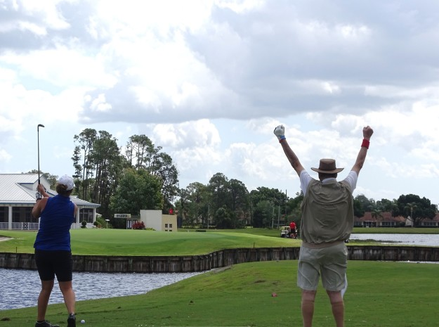 Pete Mezza (r) cheers as golf pro Gennifer Mendez (l) makes a difficult shot during the Pro-Shot for Charity